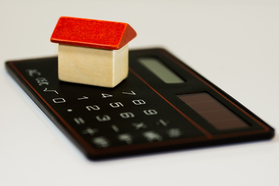 Image of a calculator and a toy-home figure.