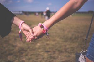 Best music festivals in America. Two girls holding hands outdoors.