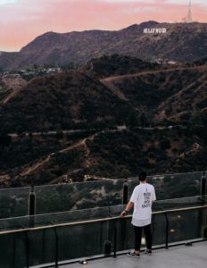 Man standing on terrace overlooking the Hollywood sign.