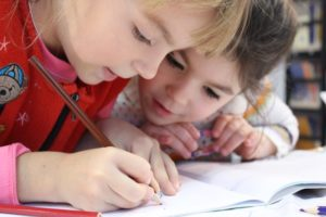 two children writing in a notebook at school after moving from California to Alabama