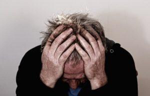 sad man holding his head