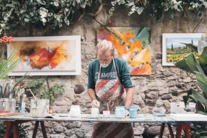 A man is moving to NYC as a professional artist and painting