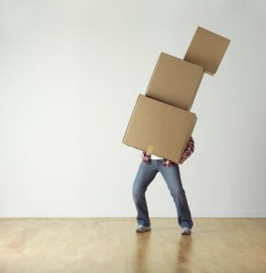 A man carrying cardboard boxes himself while trying to save money when moving cross-country.