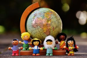 Small dolls representing people from various countries and a globe in the background.