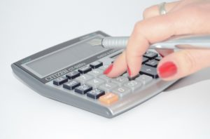 A woman calculating the costs of moving from LV to Hollywood on a calculator.