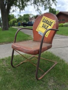 A chair with a sign for a garage sale.
