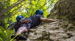 A man climbing the rock in full gear.