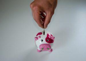 A man putting a coin in a piggy bank.