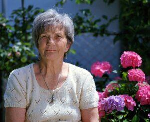 An elderly woman sitting in a garden.