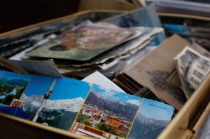 A box full of old photographs and postcards and other mementos.