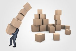 A person carrying the same moving boxes, which is one of the most common moving myths
