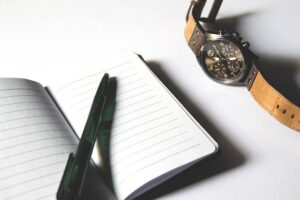 A notebook, pen and watch.