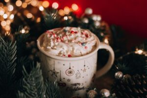 A cup of hot chocolate next to a Christmas tree you can enjoy once you successfully apply the tips for LA relocation during holidays.