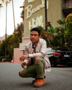 A guy in green pants in front of the famous Beverley Hills hotel.
