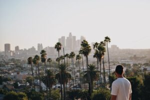 A guy standing on a hill and enjoying the view of LA.