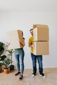 There are two people holding some cardboard boxes.