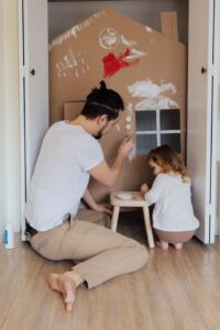 A man and a little girl are painting a cardboard house.