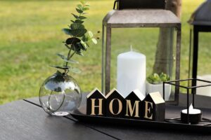 A table with a candle, a plant in a vase, and a home sign