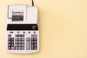 Ten key accounting calculator on yellow desk.