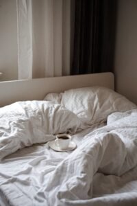 A cup of coffee  on a bed in a Bed&Breakfast