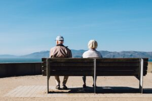 An elderly couple sitting on a bench and thinking about moving to Canada