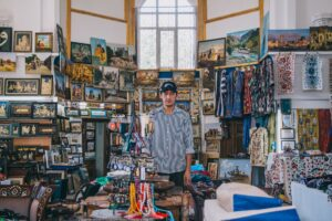 A man in a gallery with various knick-knacks
