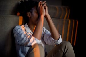 A person stressed out and sitting on the floor in a dark room.